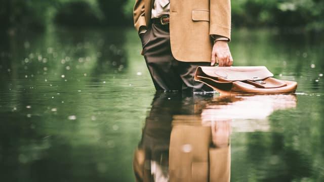 Ein Mann in Anzug und mit Ledermappe steht knietief im Wasser.
