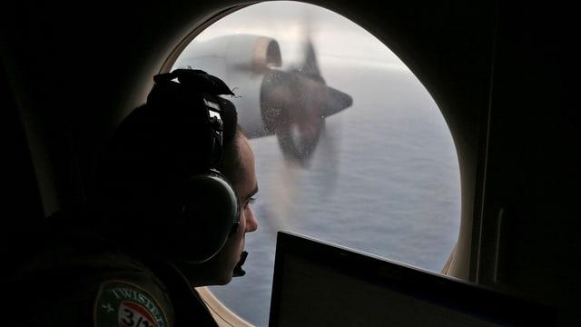 Ein Offizier blickt aus einem Flugzeug.