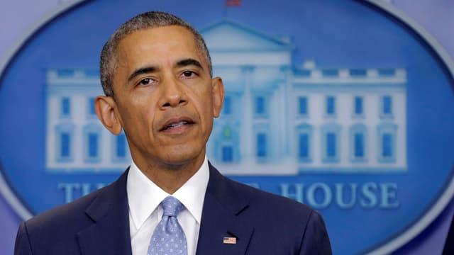 Obama spricht vor dem Emblem des Weissen Hauses.