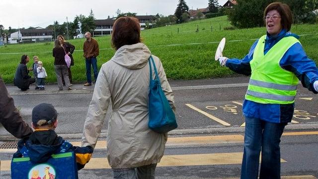 Eine Frau mit Leuchtweste gibt den Weg frei über den Fussgängerstreifen.