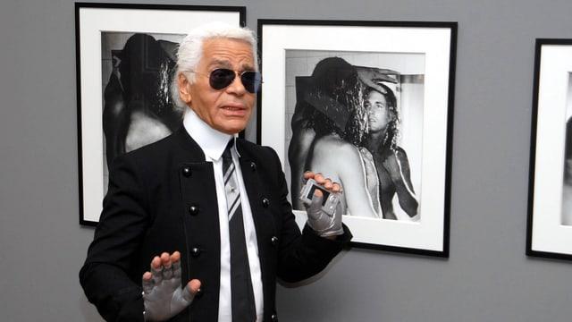 ein Mann mit Sonnenbrille steht vor gerahmten Bildern