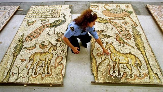 Metergrosse Steinmosaike liegen am Boden, eine Polizistenin Uniform kniet daneben.