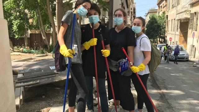 Vier junge Mädchen mit Schutzmaske und Besen in der Hand