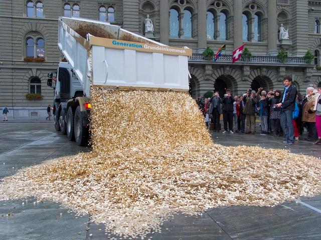 Ein Lastwagen schüttet Fünfräppler auf den Bundesplatz in Bern.