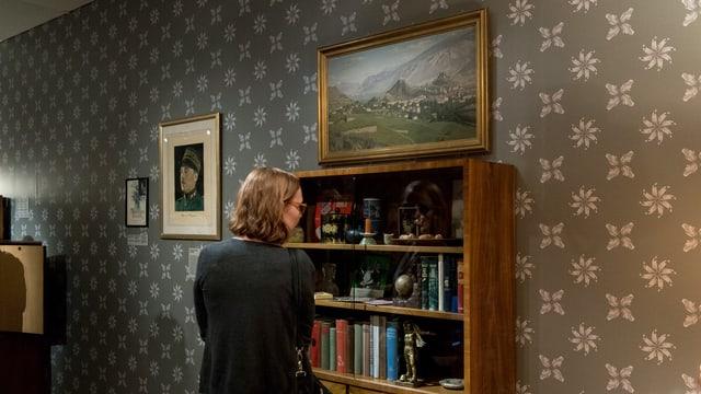 Eine Frau schaut sich eine Rekonstruktion eines Zimmers aus den 60er Jahren