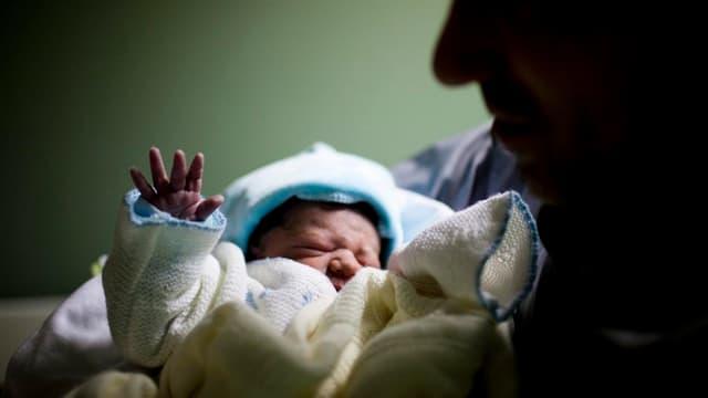 Ein Mann hält ein Neugeborenes in den Armen.