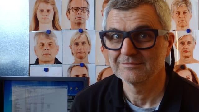 Fotograf Daniel Boschung posiert vor einer Wand mit Portraits, die vom Roboterarm gemacht wurden.