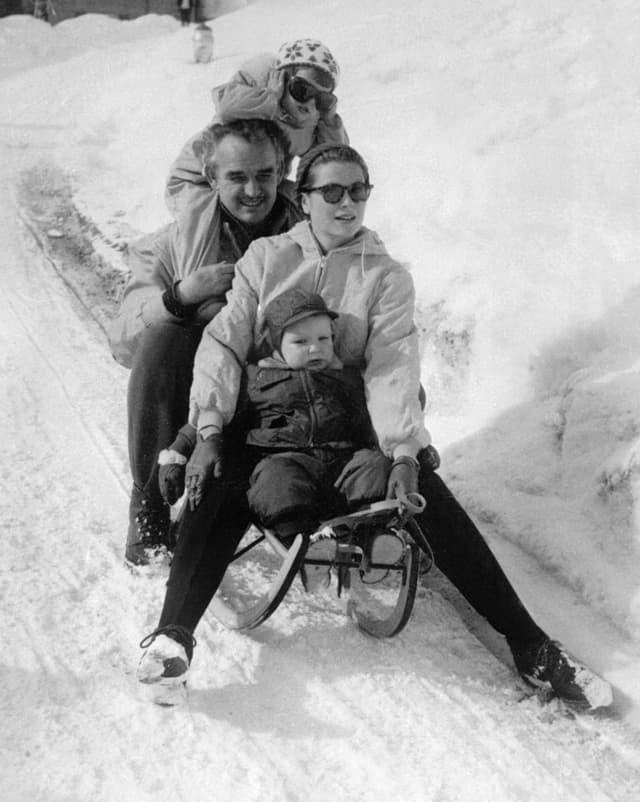Rainier und Grace Kelly mit Kindern auf einem Davoser Schlitten.