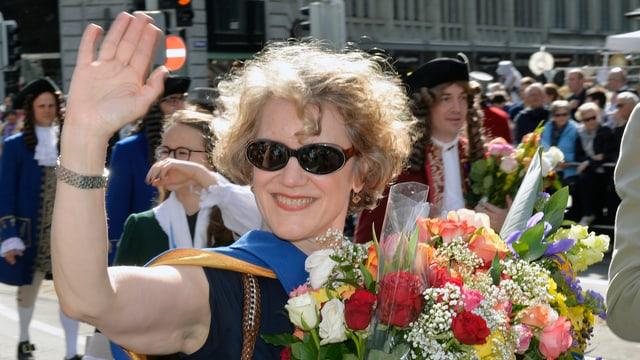 Eine Frau mit Brille und grossem Blumenstrauss