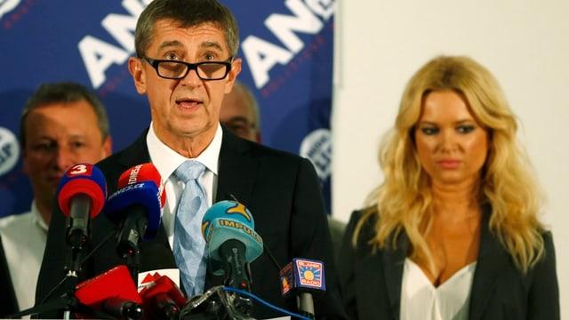 Babis hält eine Rede, die Brille vorn auf der Nase; vom Betrachter aus rechts neben ihm, etwas im Hintergrund, seine blonde Ehefrau.