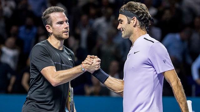 Adrian Mannarino e Roger Federer dattan il maun suenter la partida da quart final a Basilea.