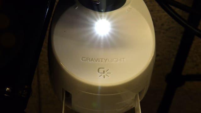 Das Gravity Light, ein Generator zum Aufhängen. An einer Kunstoffkette hängt ein schwerer Sack voller Steine, der den Generator antreibt und so Strom erzeugt.