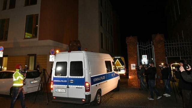 Ein Polizeiauto vor einem Gebäude, viele Medienleute