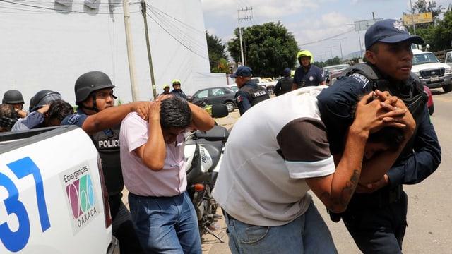 Polizisten mit Festgenommenen
