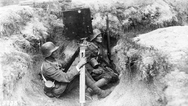 Zwei Männer sitzen mit einer Kamera im Schützengraben.