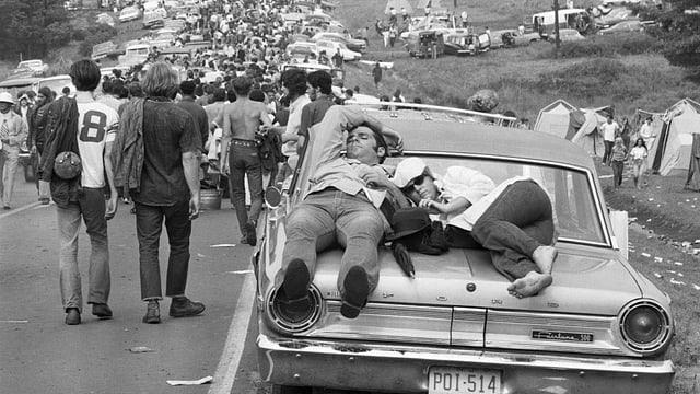 Ein Paar schläft auf der Kühlerhaube, im Hintergrund eine mit Autos und Menschen verstopfte Strasse