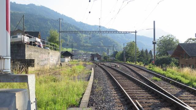 Bahnschienen, in der Ferne der Bahnhof Leissigen.