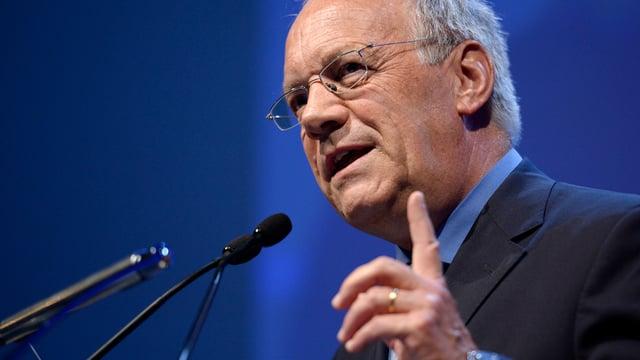 Schneider-Amman vor einem Rednerpult mit erhobenem Finger.