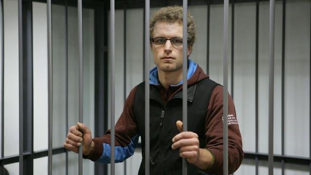 Marco Weber ist in einem Käfig eingesperrt. Er hat die Hände an den Gitterstäben und blickt in die Kamera.