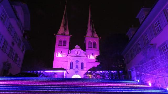 Die Hofkirche Luzern in violettem Licht.