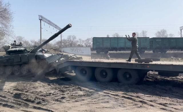 Aufladen eines Panzers auf Lastfahrzeug neben Bahngeleisen.