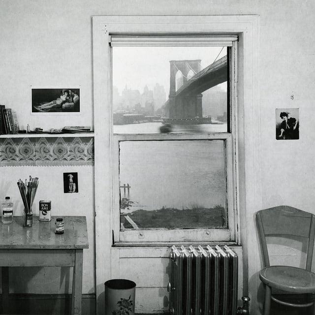 Auf einer schwarz-weissen Fotografie ist ein karg eingerichtetes Zimmer zu sehen, durch dessen Fenster die Brooklyn Bridge zu sehen ist.