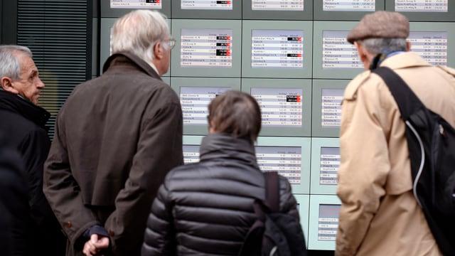Menschen begutachten Börsenkurse.