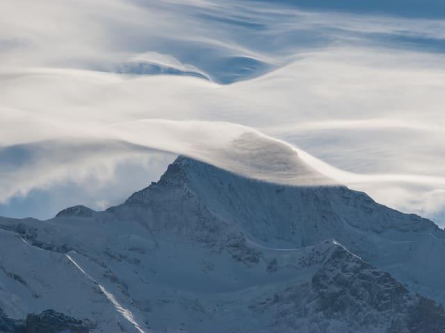 Ein Wolkenschleier legt sich im Form einer Welle über einen Alpengipfel.