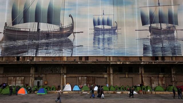 Flüchtlinge in Zelten unter einem Bild von alten Segelschiffen am Hafen von Piräus bei Athen.