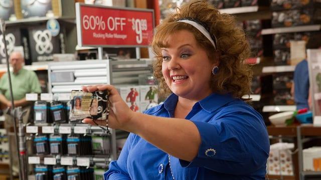 Melissa McCarthy zeigt in einem Laden ihre ID.