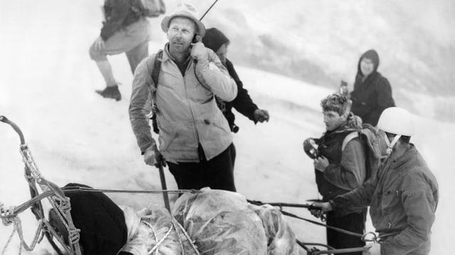 Schwarzweissfoto: Männer in Bergstigerkleidung neben einem Rettungsschlitten. Eer der Männer hält ein Telefon und blickt nach oben.
