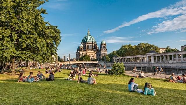Mehrere Personen sitzen auf einer Wiese bei strahlendem Wetter. Im Hintergrund is ein Dom mit grosser Kuppel zu sehen.