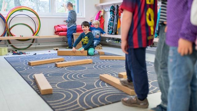 Ein Teppich, darauf liegen verteilt sechs Holzstücke, ein Kind kniet bei einer Holzlatte und lacht in die Kamera.