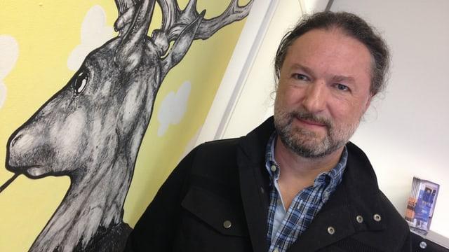 Christoph Rölli in seiner Werbeagentur in Solothurn, er posiert neben einem Bild eines Hirsches.