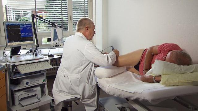 Arzt sitzt an einer Liege und hält ein Messgerät an den Unterschenkel eines Patienten.