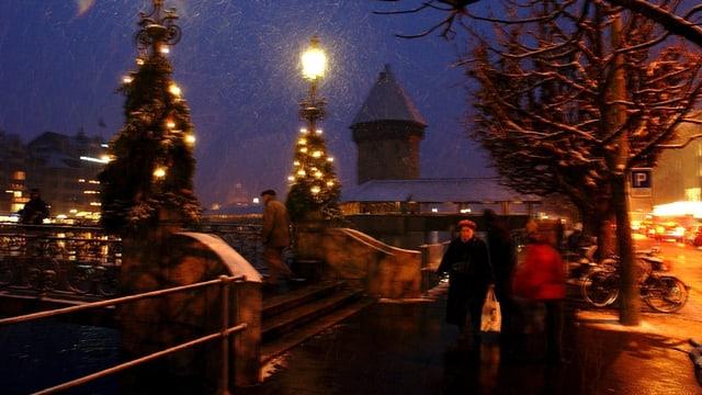 Menschen im verschneiten Luzern, im Hintergrund die Kapellbrücke.