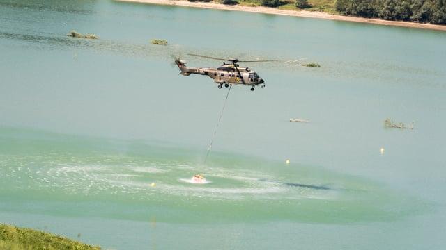 In helicopter prenda si aua dal Lai da Gruyere per furnir aua sin alps sitgas.