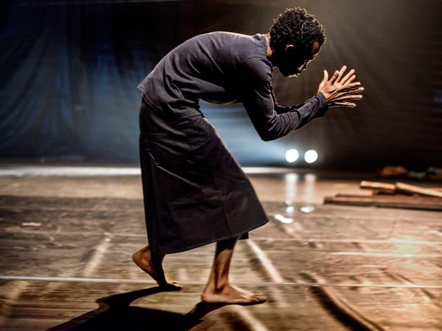 Linyekula tanzt vornübergebeugt und klatscht in die Hände.