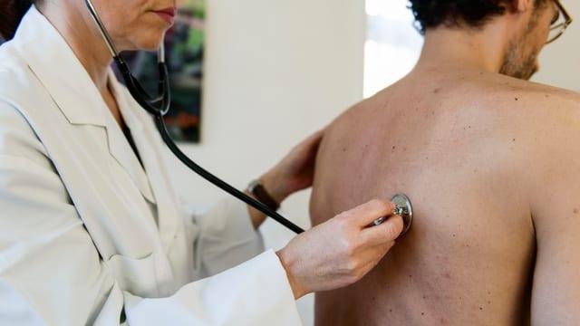 Hausärztin untersucht Patienten mit Stethoskop.