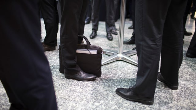 Beine von Geschäftsmännern in Anzügen und eine Aktentasche.