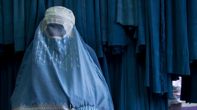 Eine Frau ist durch eine Burka verhüllt.