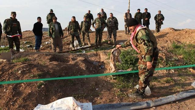 Kurdische Kämpfer an einer Stelle, wo Jesiden exekutiert worden sein sollen.