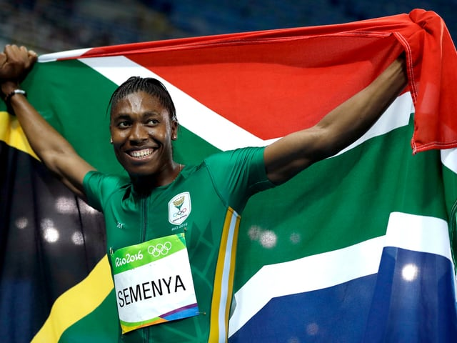 Caster Semenya hält lächelnd die südafrikanische Flagge über sich.
