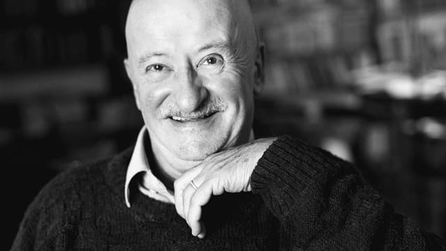 Schwarzweiss-Porträt von Giovanni Orelli, 1998 in Lugano, lächelnd vor einer Bücherwand.