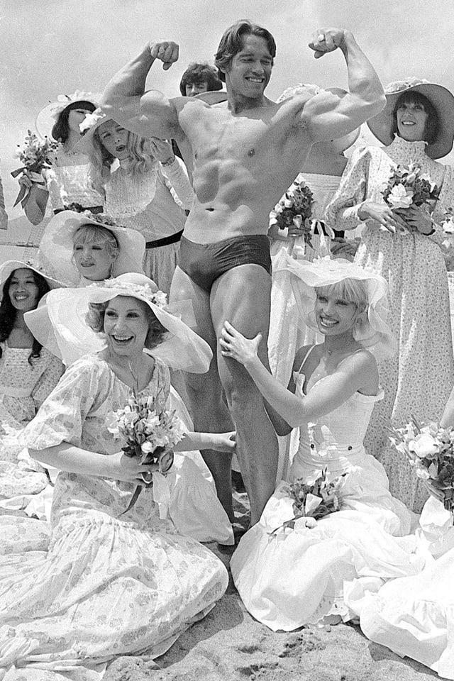 Mann in Bodybuilderpose umgeben von Frauen in langen Kleidern.