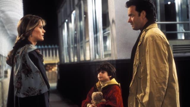 Tom Hanks und Meg Ryan schauen sich an. Ein Kind steht zwischen den beiden.