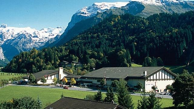 Landschaft mit Bergen und zwei Gebäuden auf einer grünen Wiese.