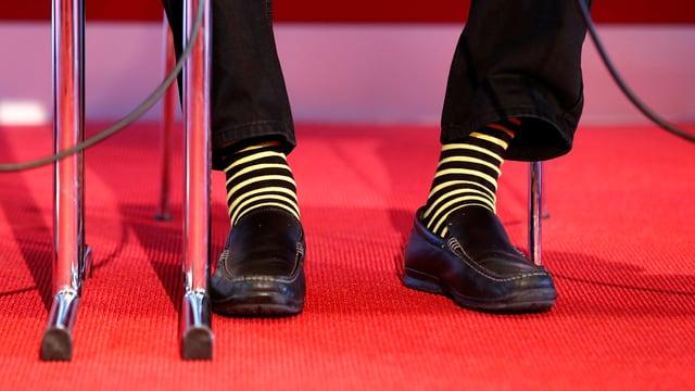 Aufnahme von Andy Rihs Füssen, die in Socken der Klubbfarbe von YB stecken.
