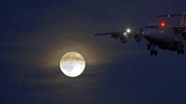 Ein Flugzeug landet in der Nacht bei Vollmond.