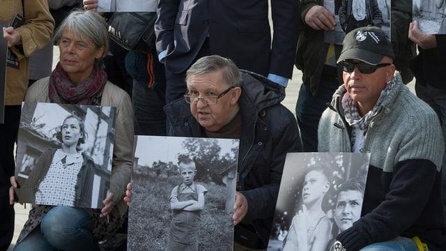 Ehemalige Verdingkinder und Opfer von fürsorgerischen Massnahmen posieren mit Kinderfotos vor dem Bundeshaus in Bern.